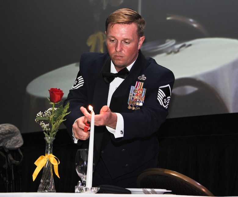 U.S. Air Force Master Sgt. Christopher Cochran, 355th Equipment Maintenance Squadron munition systems section chief, lights a candle at the Missing Man Table during an Air Force Ball at the Tucson Convention Center, in Tucson, Ariz., Sept. 12, 2015. The table is set to honor those killed in action, missing in action, or deployed who could not join in celebration. (U.S. Air Force photo by Airman 1st Class Ashley N. Steffen/Released)