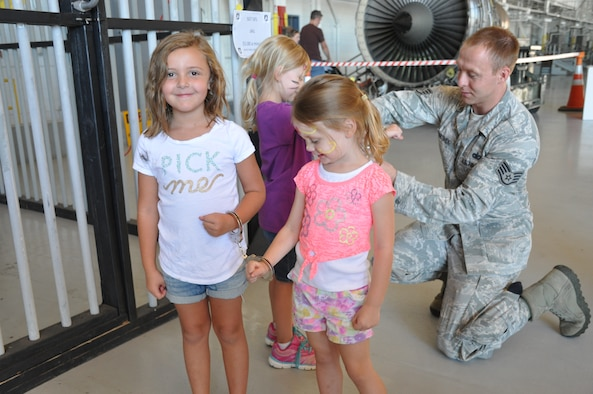 Staff Sgt. Samuel Martinek of the 507th Security Forces Squadron handcuffs kids to put them in jail during the 507th Air Refueling Wing Family Day celebration Sept. 12, 2015, at Tinker Air Force Base, Okla. Family Day is held on the Saturday of the Unit Training Assembly and gives Reservists and their families time to come together and build camaraderie. (U.S. Air Force photo by Tech. Sgt. Lauren Gleason)