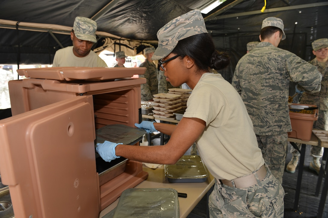 Airman First Class Rebecca Hammock, Senior Airman Taiheem Pleasant and Airman Ethan Haberman, members of the 155th Services Flight, prepare and serve meals to Airmen at the 155th Air Refueling Wing during a Domestic Operations training session, showcasing the Nebraska Air National Guard's capabilities in emergency management to Nebraska Civil leaders, June 5, at the Nebraska National Guard air base, Lincoln, Neb.