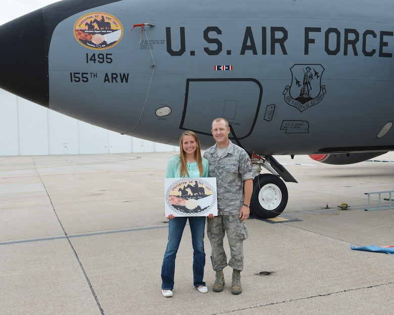 Mariah Harm, a Stapleton, Neb., native and senior at Stapleton High School, holds her original artwork submission with Senior Master Sgt. Chad Martin, the director of the Nebraska Community Nose Art Program, after she unveiled her artwork on the nose of a KC-135R Stratotanker at the 155th Air Refueling Wing, Nebraska Air National Guard Base Aug. 8, in Lincoln, Neb.