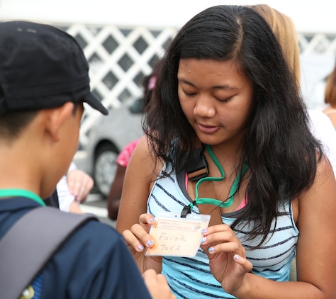 Faith Lobaton, a senior at Matthew C. Perry High School aboard Marine Corps Air Station Iwakuni, Japan, introduces herself to a student from Yanai City High School Aug. 22, 2015. The students were given name tags with English letters and Japanese characters so the students could read and understand each other's names.