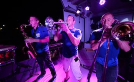 The Air Forces Central Command band horn section, perform for service members during a concert at an 