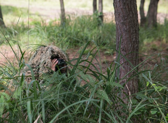 Japanese Ground Self-Defense Force Sgt. Akito Yagi looks through binoculars at the target while performing stalking drills during Forest Light 16-1 at Camp Imazu, Takashima, Japan, Sept. 10, 2015. The Marines sat up on a high embankment trying to catch the JGSDF stalking the target with binoculars. Forest Light is a semiannual, bilateral exercise consisting of a command post exercise and multiple field training events, conducted by elements of III Marine Expeditionary Force and the JGSDF. Yagi is a sniper with 50th Infantry Regiment, 14th Brigade.