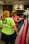 Courtney McDaniel, wife of Sgt. 1st Class Jason McDaniel, 2nd Battalion, 70th Armor Regiment, 2nd Armored Brigade Combat Team, 1st Infantry Division, looks through the racks of ball gowns the Fort Riley USO provided during Operation Gift the Gown Aug. 29.  The ball McDaniel is preparing for is scheduled for Oct. 2.