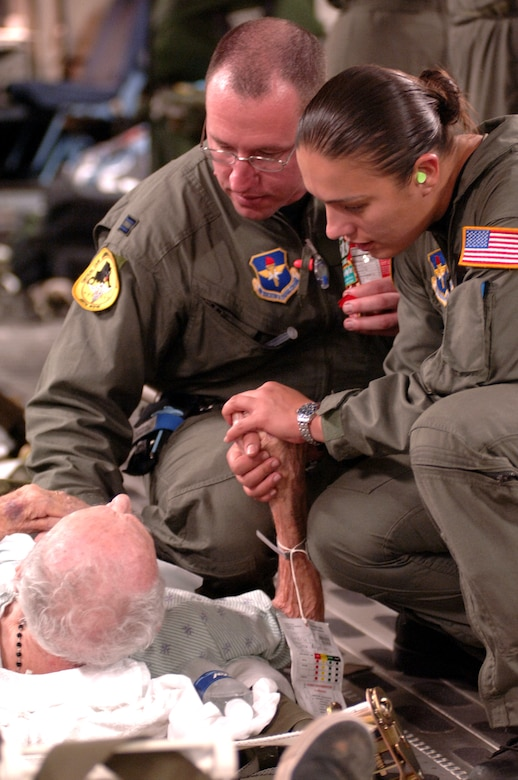 Capt. Mike Dixon, ICU nurse with the 59th Medical Wing and Staff Sgt. Lina Gamez , respiratory therapist with the 759th MSGS, provide a hand to hold and reassuring words to an elderly patient and survivor of hurricane Katrina.  They are traveling, om 1 Sept. 2005, aboard a C-17 Globemaster III assigned to the 446th Airlift Squadron, McChord Air Force Base.  Dixon and Gamez are stationed at Lackland Air Force Base, TX, and have teamed up with the activated Reserve crew from McChord to provide aeromedical evacuation for ambulatory and critical care patients in New Orleans.  This 1.5 hour flight carried 28 ambulatory and 6 litters to Dobbins Air Force Base, GA. (U.S. Air Force photo Master Sgt. Lance Cheung)