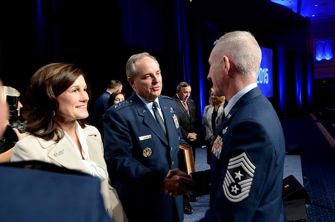 Air Force Chief of Staff Gen. Mark A. Welsh III (center) and his wife, Betty, are congratulated by an Air Force command chief master sergeant after Chief Master Sgt. of the Air Force James A. Cody presented Welsh with an invitation to an Order of the Sword ceremony following Cody's Enlisted Force Update at the Air Force Association's Air and Space Conference and Technology Exposition Sept. 16, 2015, in Washington, D.C. (U.S. Air Force photo/Scott M. Ash)