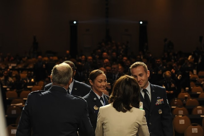 Tech. Sgt. Torri Hendrix and Staff Sgt. Carlin Leslie, members of the Secretary of the Air Force Public Affairs command information section, congratulate Chief of Staff of the Air Force Gen. Mark A. Welsh III and his wife, Betty, on receiving the invitation to the Order of the Sword ceremony during Chief Master Sgt. of the Air Force James A. Cody's Enlisted Force Update at the Air Force Association Air and Space Conference and Technology Exposition Sept. 16, 2015. The Order of the Sword was established by the Air Force enlisted force to recognize and honor military senior officers, colonel or above, and civilian equivalents, for conspicuous and significant contributions to the welfare and prestige of the Air Force enlisted force, mission effectiveness and the overall military establishment.  (Air Force photo by Staff Sgt. Whitney Stanfield)