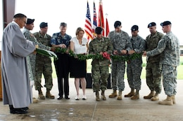 Brig. Gen. Jeffrey L. Milhorn, Commander Pacific Ocean Division, U.S. Army Corps of Engineers, (center) is assisted in the traditional maile lei untying and ribbon-cutting ceremony  by Lt. Col. Christopher W. Crary, Commander, U.S. Army Corps of Engineers-Honolulu District (third from left,) Mr. Len Housley, Deputy Commander U.S. Army Garrison-Hawaii (fourth from left),  Mrs. Sally Pfenning, Director, Directorate of Public Works, USAG-HI (fifth from left), Lt. Col. Michael Binetti, Commander, 29th Brigade Engineer Battalion (fourth from right),  Maj. Chris Izquierdo, Executive Officer, 19th Military Police (CID) Battlion (third from right), and Capt. Michael Simmons, Commander, A Company, 249th Engineer Battalion (Prime Power) (second from right). The Rev. Sherman Thompson (left) led the Hawaiian blessing and maile lei ribbon untying cutting ceremony.