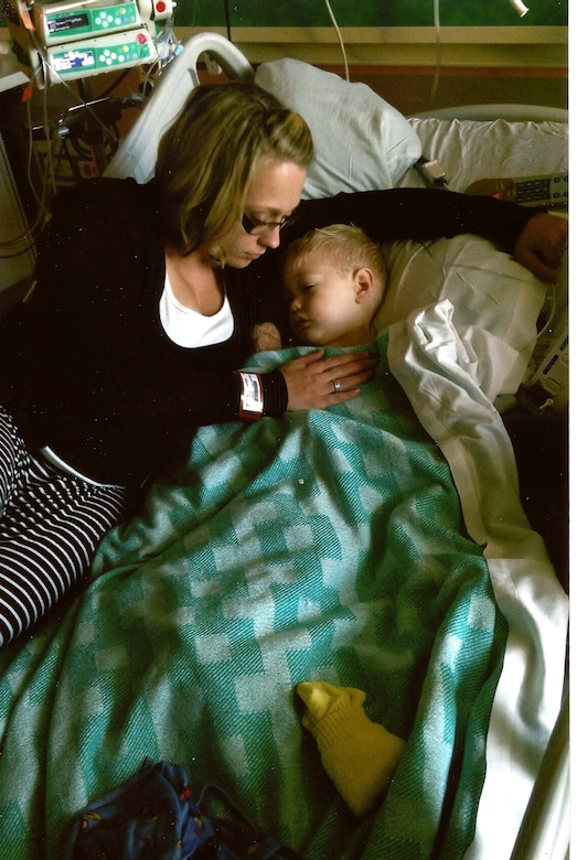 Jaycee Boyer, wife of Tech. Sgt. Tim Boyer, 56th Fighter Wing Public Affairs media operations NCO in charge, comforts Paul, 2, after his surgery on his brain due to a tumor in Ariz. (Courtesy photo)
