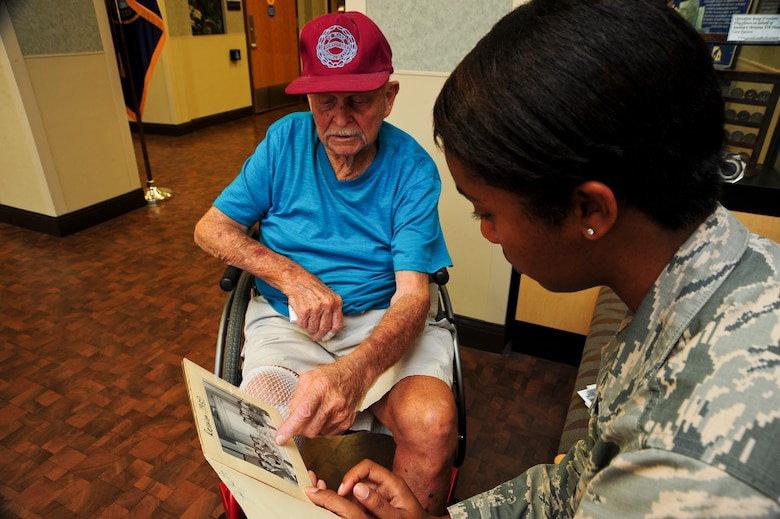 Malcolm Johnson, World War II veteran and former prisoner of war, shows U.S. Air Force Airman 1st Class Mya Crosby, 355th Fighter Wing Public Affairs photojournalist, a reunion photo of himself and fellow POWs at the Tucson Veterans Center in Tucson, Ariz., Aug. 18, 2015. Johnson was a civilian contractor when he was captured in December 1941, then put into internment camps throughout China and Japan for nearly four years. (U.S. Air Force photo by Senior Airman Chris Massey/Released)