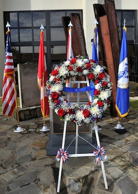 A wreath of red, white and blue flowers stands in front of the charred granite stone from the Pentagon at the 601st Air and Space Operations Center's 9/11 Memorial Sept. 11. Placement of the wreath was part of a remembrance ceremony. (U.S. Air Force Photo by Airman 1st Class Sergio A. Gamboa/Released)
