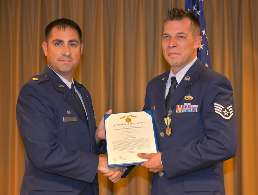 Major Robert Wryder Jr., 437th Aircraft Maintenance Squadron commander, presents the Air Force Commendation medal to SSgt. Marcus Williams, a 437th AMXS hydraulics craftsman, in the 437th AMXS auditorium at Joint Base Charleston – Air Base, Sept. 16, 2015. Williams received this reward for saving a civilian's life after a motorcycle accident. (U.S. Air Force photo/Airman 1st Class Thomas T. Charlton)