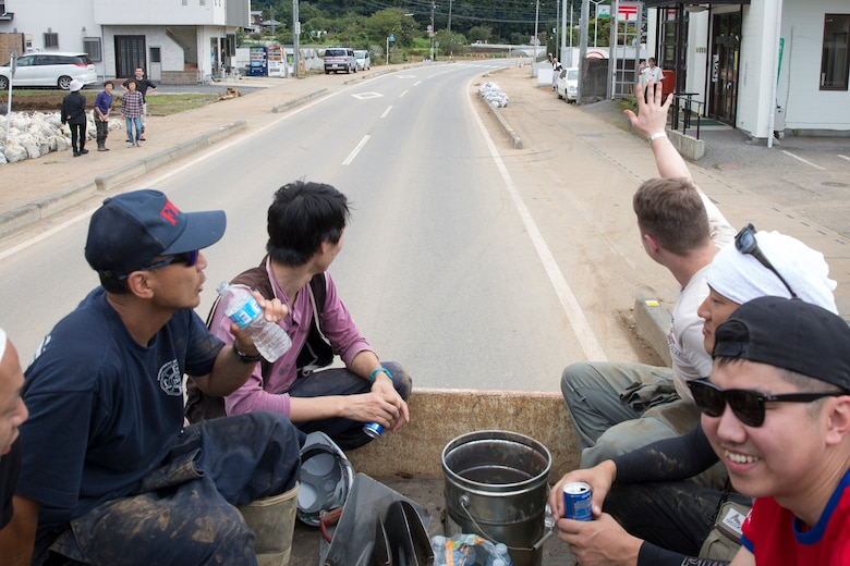 Volunteers from the 374th Civil Engineer Squadron greet residents from the back of a pickup truck after finishing cleaning an area of Kanuma City, Tochigi Prefecture, Japan, Sept. 15, 2015. Sixty Airmen and civilians from the 374th CES volunteered to help at sites in the Kasono area in support of floods and landslides caused by the heavy rainfall associated with the post-tropical remnant of Tropical Storm Etau, which stalled over eastern Japan, dumping up to 17 inches of rain in 24 hours, from Sept. 10 to Sept. 11. (U.S. Air Force photo by Osakabe Yasuo/Released)