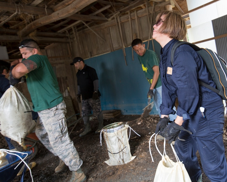 Volunteers from the 374th Civil Engineer Squadron carry bags full of mud from a house at Kanuma City, Tochigi Prefecture, Japan, Sept. 15, 2015. Sixty Airmen and civilians from the 374th CES volunteered to help at sites in the Kasono area in support of floods and landslides caused by the heavy rainfall associated with the post-tropical remnant of Tropical Storm Etau, which stalled over eastern Japan, dumping up to 17 inches of rain in 24 hours, from Sept. 10 to Sept. 11. (U.S. Air Force photo by Osakabe Yasuo/Released)