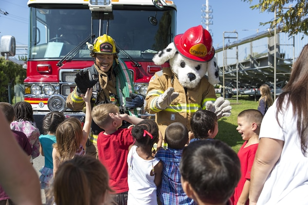 Students with Matthew C. Perry Elementary School gather around to greet Eiji Aridome, a fire fighter aboard station, and, Sparky,  the air station's fire safety dog, during M.C. Perry Elementary and High School's 9/11 Remembrance Walk aboard Marine Corps Air Station Iwakuni, Japan, Sept. 11, 2015.  Beginning at 9:11 a.m., this is the third annual walk hosted by the schools and an event that helps students understand the significance of never forgetting, according to Devin Johnston-Lee, fire chief for the air station.