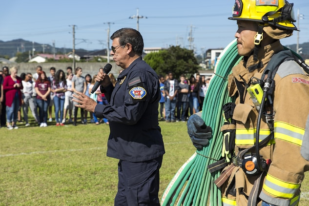 Devin Johnston-Lee, fire chief for the air station, speaks to Matthew C. Perry Elementary and High School students during M.C. Perry Elementary and High School's 9/11 Remembrance Walk aboard Marine Corps Air Station Iwakuni, Japan, Sept. 11, 2015.  Johnston-Lee spoke to the students about the importance of remembering 9/11 and getting them to understand that everyday citizens do heroic things, not because they're not afraid, but because they are afraid and are still willing to do their job.