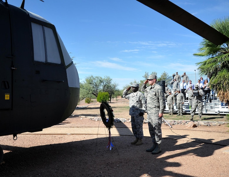 Army Staff Sergeant Maurice Liggins, a recruiter from the Tucson Recruiting Company, and Senior Airman Christopher Martin, 305th Rescue Squadron aviation resource manager render salutes at the static display model of a CH-3E Jolly Green Giant helicopter similar to the own flown by the aircrew of flight PONY 1-2 at Heritage Park, Davis-Monthan AFB. 943rd RQG Airmen past and present gathered to remember the men who died during a nighttime training mission aboard a CH-3E Jolly Green Giant Helicopter. (U.S. Air Force Photo/ Tech. Sgt. Carolyn Herrick)