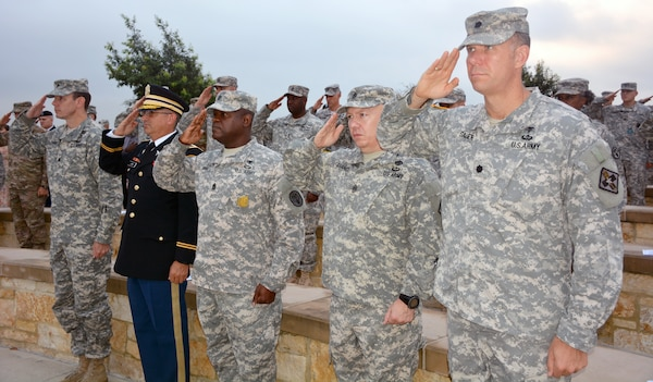Members and friends of the U.S. Army Medical Service Corps salute during the playing of the National Anthem at the  US Army Medical Service Corps 9/11 Remembrance Ceremony at the Fort Sam Houston National Cemetery, held in honor of the Medical Service Corps officers who paid the ultimate sacrifice as a result of the terrorist attack on Sept. 11, 2001 and in support of combat operations.