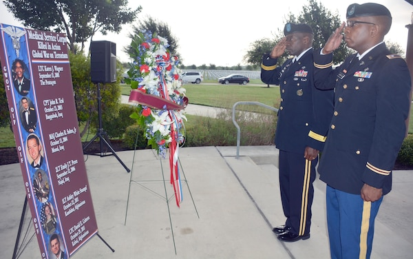 Brig. Gen. R. Scott Dingle (left), U.S. Army Medical Command deputy chief of staff for operations, and Lt. Col. Marion Jefferson, executive officer, Office of the Chief, Medical Service Corps, salute to the sounds of taps during the presentation of a wreath in honor of fallen Medical Service Corps officers at a Sept. 11 remembrance ceremony held at the Fort Sam Houston National Cemetery.