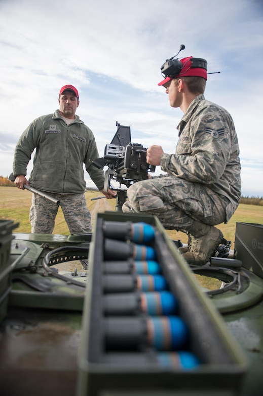 Combat arms training instructors Senior Airman Jordan Thompson (right), 168th Alaska Air National Guard, and Staff Sgt. Gregory Chmielewski, 354th Security Forces Squadron, replace the barrel on a Mark 19 grenade launcher during training Sept. 9, 2015, at Eielson Air Force Base, Alaska. Thompson and Chmielewski were training members of the 354th Security Forces Squadron on the weapon. (U.S. Air Force photo by Staff Sgt. Shawn Nickel/Released)