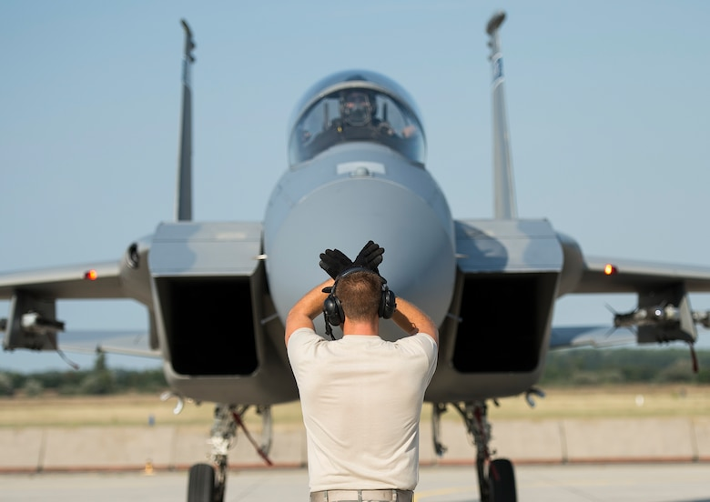 A crew chief from the 123rd Expeditionary Fighter Squadron marshals an F-15 Eagle fighter aircraft at Kecskemet Air Base, Hungary, Sept. 3, 2015. Four Oregon Air National Guard F-15s forward deployed to Hungary from Campia Turzii, Romania, as part of Operation Atlantic Resolve, improving interoperability between NATO allies and ensuring the continued stability of the region. (U.S. Air Force photo/Staff Sgt. Chad Warren)