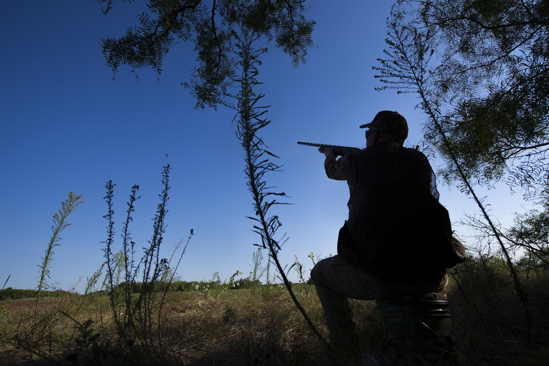 Staff Sgt. Daniel Cole, 364th Training Squadron instructor, points his shotgun at a dove passing by during the dove hunt portion of the Clay County Dove Salute in Henrietta, Texas, Sept. 12, 2015. Airmen were invited to the Birdwell and Clark Ranch to participate in dove hunt and a Texas-style steak dinner. (U.S. Air Force photo by Senior Airman Kyle Gese)