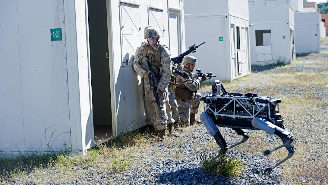 "Spot, a quadruped prototype robot, aids Marines in clearing a room during a demonstration at Marine Corps Base Quantico, Va., Sept. 16, 2015. Employees of the Defense Advanced Research Projects Agency trained Marines from the Marine Corps Warfighting Lab how to operate ""Spot""."