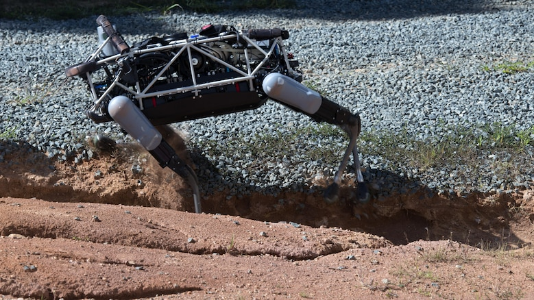 """Spot"", a quadruped prototype robot, maneuvers through a ditch during a demonstration at Marine Corps Base Quantico, Va.,Sept. 16, 2015. Employees of the Defense Advanced Research Projects Agency trained Marines from the Marine Corps Warfighting Lab how to operate ""Spot""."