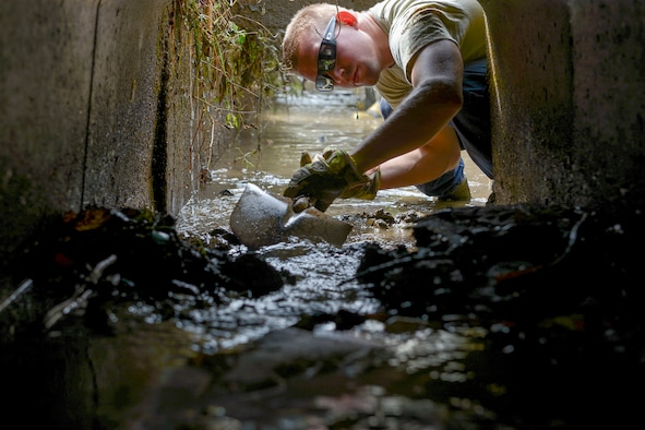 U.S. Air Force Airman 1st Class Thomas Smith, 374th Civil Engineer Squadron fire protection, shovels mud from an irrigation system at Kanuma City, Tochigi prefecture, Sept. 15, 2015. Smith and other members of a large volunteer force from Yokota Air Base ventured to Tochigi to assist the locals with mud removal, sand bagging and fixing what was broken during a recent flood and landslide. (U.S. Air Force photo by Staff Sgt. Cody H. Ramirez/Released)