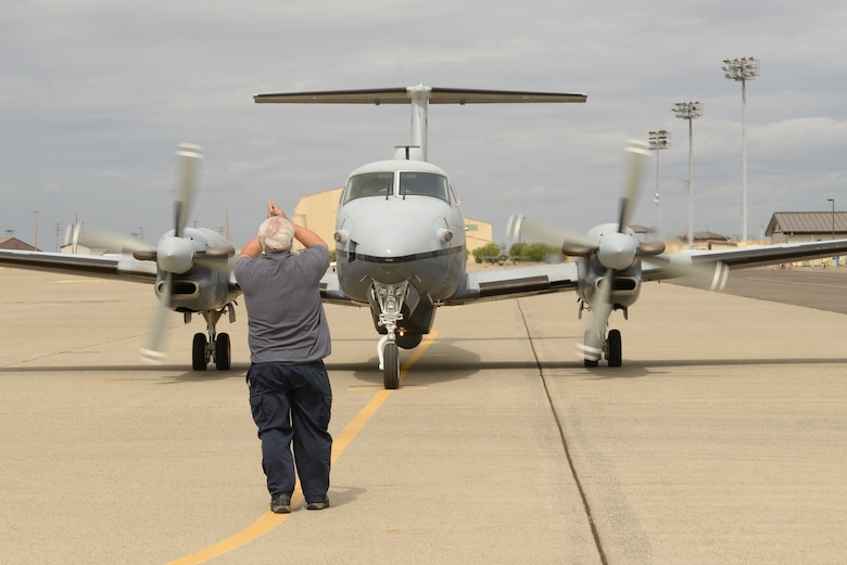 A member of L3 Communications prepares the aircrew of an MC-12W Liberty to takeoff Sept. 16, 2015, at Beale Air Force Base, California. Beale Airmen conducted the aircraft's final flight with Air Combat Command. The MC-12W is a medium- to low-altitude, twin-engine turboprop aircraft, which provides intelligence, surveillance and reconnaissance support directly to ground forces. (U.S. Air Force photo by Airman 1st Class Ramon A. Adelan)