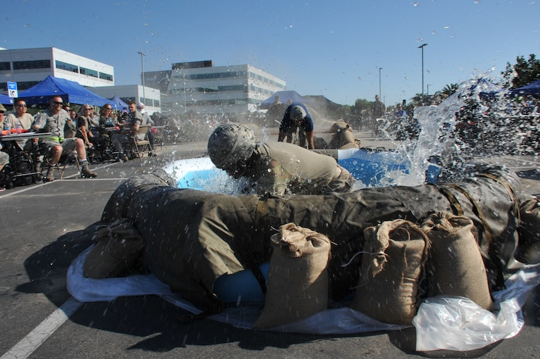 """A """"Warrior of the Mess"""" makes a big splash after breaking the rules of engagements and compelled to complete an obstacle course during the Space and Missile Systems Center Combat Dining Out held at Los Angeles Air Force Base in El Segundo, Calif. (U.S. Air Force photo/Sarah Corrice)"""