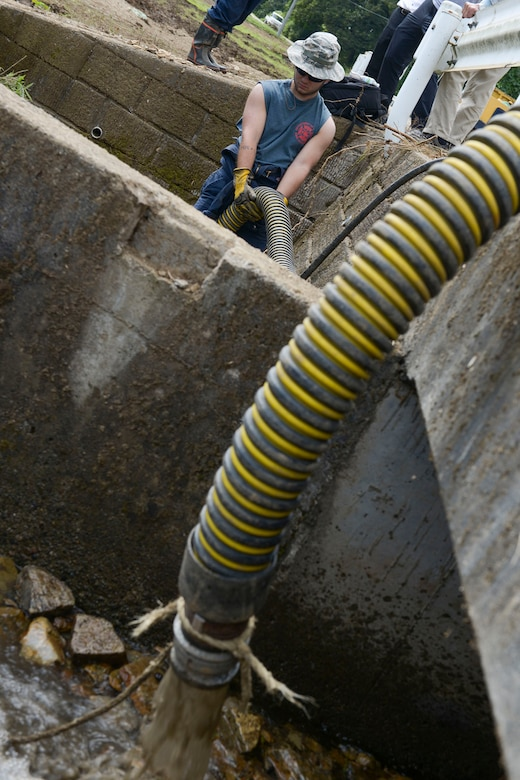 Airman 1st Class Jordan Spiceland, 374th Civil Engineer Squadron fire protection services, pumps water from a clogged irrigation drain at Kanuma City, Tochigi Prefecture, Japan, Sept. 15, 2015. Ten consecutive days of rain led to flooding and landslides that damaged much of the local area. More than 60 volunteers from Yokota Air Base ventured to the prefecture to assist with post-damage relief. (U.S. Air Force photo by Staff Sgt. Cody H. Ramirez/Released)