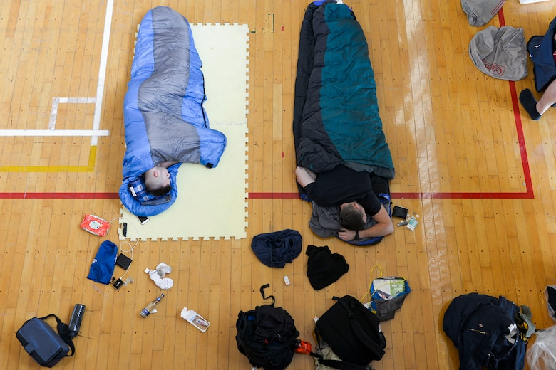 Volunteers with the 374th Civil Engineer Squadron sleep on the gym floor of a local elementary school at Kanuma City, Tochigi prefecture, Japan, Sept. 15, 2015. More than 20 of 60 volunteers stayed in the elementary's gym for two nights while assisting in flood relief efforts in the Tochigi area. (U.S. Air Force photo by Staff Sgt. Cody H. Ramirez/ Released)