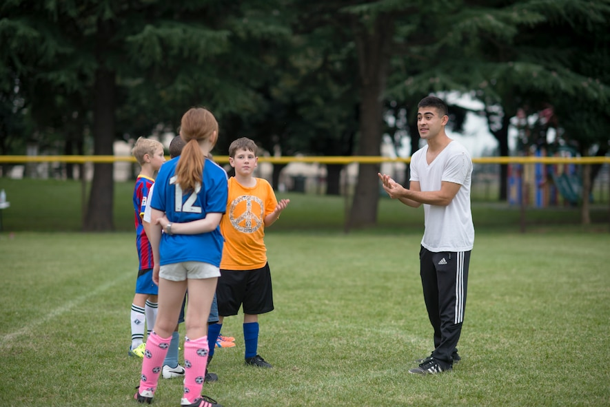 Airman 1st Class Tomasz Barba, volunteer soccer coach, discusses the importance of communication with youth soccer participants at Yokota Air Base, Japan, Sept. 15, 2015. Barba, a rookie coach, asked his players to help him out by providing any input they had regarding his style. (U.S. Air Force photo by Airman 1st Class Delano Scott/Released)