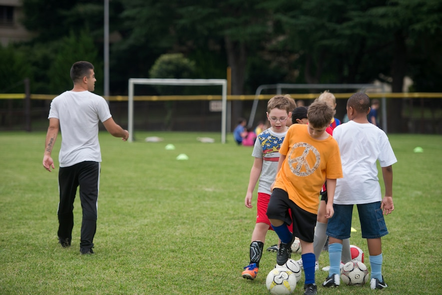 Airman 1st Class Tomasz Barba, volunteer soccer coach, instructs youth soccer participants about their next drill at Yokota Air Base, Japan, Sept. 15, 2015. Outside of developing soccer skills, Barba said that he also tries to instill the value of respect into his players. (U.S. Air Force photo by Airman 1st Class Delano Scott/Released)