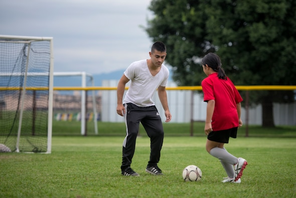 Airman 1st Class Tomasz Barba, volunteer soccer coach, practices a handling technique with a youth soccer participant at Yokota Air Base, Japan, Sept. 15, 2015. Yokota's Youth Sports Program is extensive and relies upon hundreds of volunteers to serve as coaches, assistant coaches, and team parents. (U.S. Air Force photo by Airman 1st Class Delano Scott/Released)