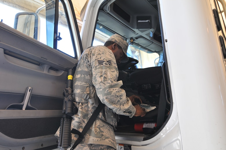 U.S. Air Force Senior Airman Henry Lanier, with the New Jersey Air National Guard's 177th Maintenance Squadron, inspects a commercial vehicle entering the Atlantic City Air National Guard Base, Sept. 16, 2015 while serving as a security forces augmentee. Airmen from different career fields can serve as augmentees after undergoing the required training in order to assist the base in times of low manning. (U.S. Air National Guard photo by Senior Airman Amber Powell/Released)