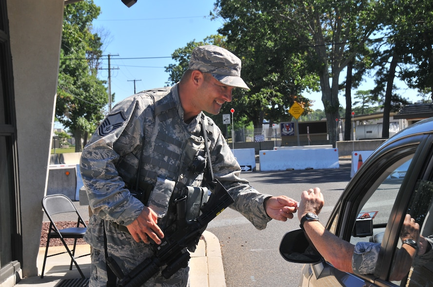 U.S. Air Force Master Sgt. Todd Butcher, civil engineer with the New Jersey Air National Guard's 177th Fighter Wing, checks the military ID of someone entering the Atlantic City Air National Guard Base, Sept. 15, 2015 while serving as a security forces augmentee. Airmen from different career fields can serve as augmentees after undergoing the required training in order to assist the base in times of low manning. (U.S. Air National Guard photo by Senior Airman Amber Powell/Released)