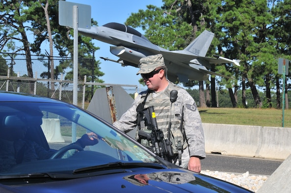 U.S. Air Force Staff Sgt. Ryan Fogarty, fire protection specialist with the New Jersey Air National Guard's 177th Fighter Wing, checks the military ID of someone entering the Atlantic City Air National Guard Base, Sept. 15, 2015 while serving as a security forces augmentee. Airmen from different career fields can serve as augmentees after undergoing the required training in order to assist the base in times of low manning. (U.S. Air National Guard photo by Senior Airman Amber Powell/Released)