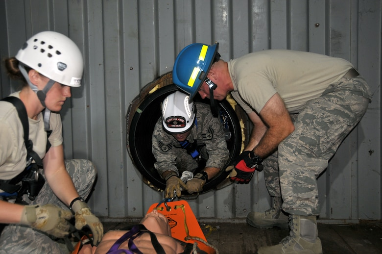 Staff Sgt. Jennifer Bristol and Staff Sgt. Christopher Meyer (center) rescue a victim as Tech. Sgt. Brian Kissinger (right) assists during confined space training for the 109th Fire Department's search and rescue team at Stratton Air National Guard Base, New York, on Sept. 17, 2015. The 12-person search and rescue team trains monthly on various rescue techniques. (U.S. Air National Guard photo by Tech. Sgt. Catharine Schmidt/Released)