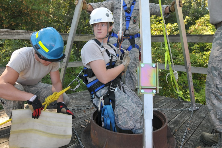 The 109th Fire Department's search and rescue team prepare to lower Staff Sgt. Jennifer Bristol during confined space training for the team at Stratton Air National Guard Base, New York, on Sept. 17, 2015. The 12-person search and rescue team trains monthly on various rescue techniques. (U.S. Air National Guard photo by Tech. Sgt. Catharine Schmidt/Released)