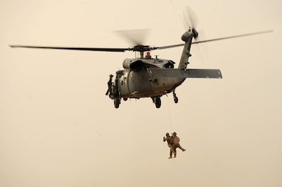 U.S. Air Force pararescuemen are hoisted into an HH-60G Pave Hawk helicopter during training at an undisclosed location in Iraq, Sept. 15, 2015. Pararescuemen are on 24-hour alert and train extensively in emergency medical tactics, combat survival, and personnel recovery to support Operation Inherent Resolve. (U.S. Air Force photo/Tech. Sgt. Brittany E. Jones)