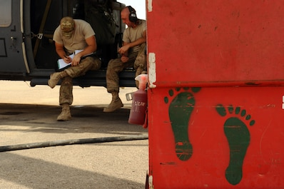 "U.S. Air Force Staff Sgt. Dylan Eichmann and Senior Airman John Morrison, 64th Expeditionary Helicopter Maintenance Unit dedicated crew chief and assistant dedicated crew chief, finish preflight checks on an HH-60G Pave Hawk helicopter in Iraq, Sept. 15, 2015. The ""Jolly Green"" footprints were the idea of Chief Master Sgt. Wayne Fisk, a prior pararescueman, and are still the symbol of the U.S. Air Force rescue community today. (U.S. Air Force photo/Tech. Sgt. Brittany E. Jones)"