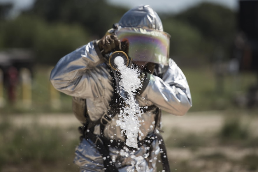 First Lt. Clayton Schmitt, a 902nd Security Forces Squadron operations officer, shoots a stream of water from a fire hose during the 2015 Battle of the Badges Sept. 12, 2015, at Joint Base San Antonio-Randolph, Texas. This year's Battle of the Badges included three main events: a tactical shooting challenge, firefighter combat challenge and fire truck pull. U.S. Air Force photo/Airman 1st Class Stormy Archer)