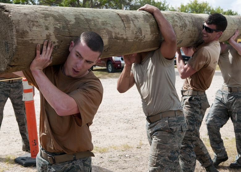 Airmen perform as a team during the Team Pain portion of the 2015 Crow Creek Challenge, Sept. 11, 2015, on F.E. Warren Air Force Base, Wyo. This event consisted of five four-man push-ups, a tire flips for 25-meters and a log carry of 25-meters. (U.S. Air Force photo by Airman 1st Class Malcolm Mayfield)