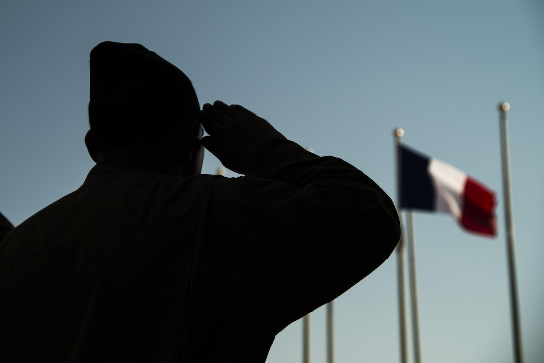 A Combined Air Operations Center member salutes the French Flag during the French National Day Parade September 14, 2015 at Al Udeid Air Base, Qatar. The parade was the commemoration of the death of WWI French pilot Capt Georges Guynemer, in Polkapelle, on September 11th, 1917. Since 1923, the French Air Force has organized a parade to start or close the day in remembrance of him.  (U.S. Air Force photo by Tech. Sgt. Rasheen Douglas)