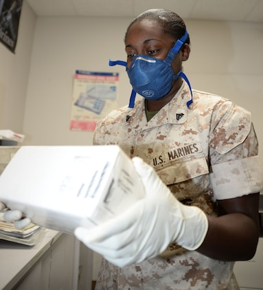 Cpl. Shada Middleton, postal clerk, Marine Corps Logistics Base Albany, demonstrates, Sept. 17, how to properly wear her personal protection equipment, a mask and latex gloves, if she encounters a suspicious piece of mail.