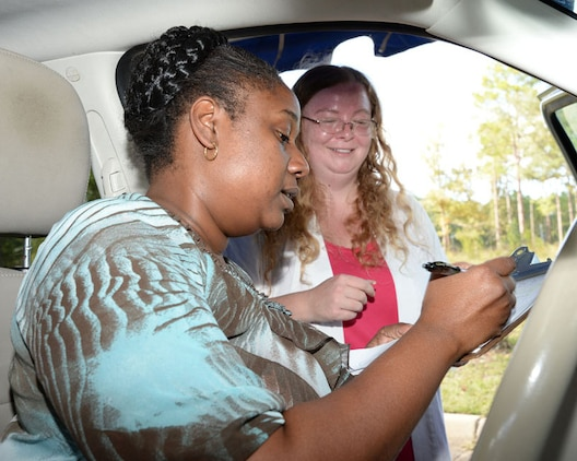 Lisa Johnson, (left) pre-kindergarten teacher, Child Development Center, Marine Corps Logistics Base Albany, completes the process of receiving a new car seat from Alisha Enfinger, MCCS' safety officer and certified child passenger safety technician, at the car seat safety check point at the CDC, Sept. 17.
