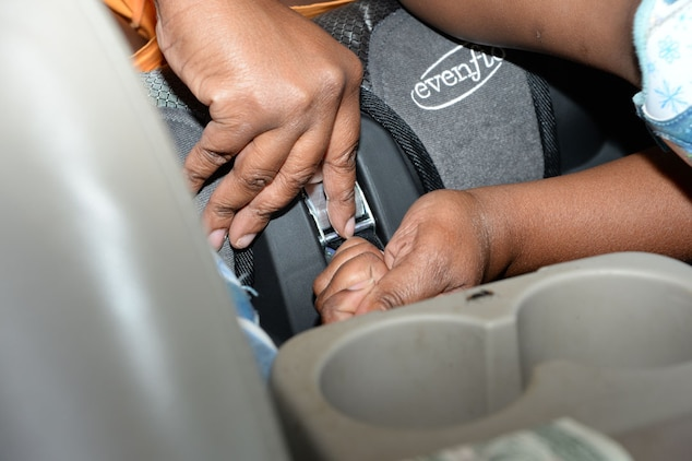 Lisa Johnson, pre-kindergarten teacher, Child Development Center, Marine Corps Logistics Base Albany, straps in her daughter at the annual car seat safety check point at the CDC, Sept. 17.