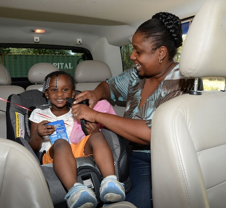 Lisa Johnson, (right) pre-kindergarten teacher, Child Development Center, Marine Corps Logistics Base Albany, straps in her daughter at the annual car seat safety check point at the CDC, Sept. 17.